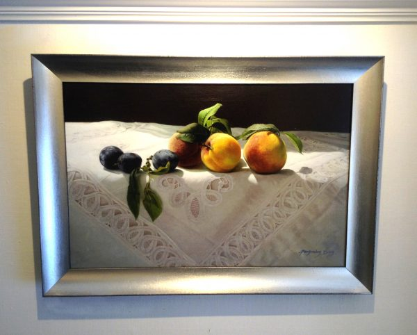 framed Fenming Ding painting of peaches on a white tablecloth