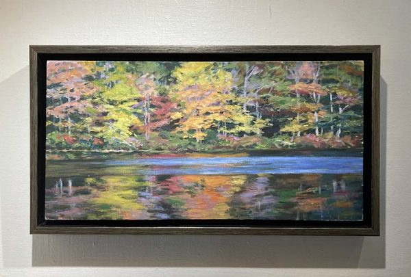 framed Lynne Adams painting of woods at edge of water in autumn