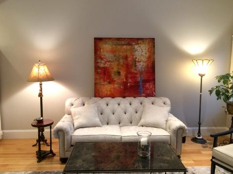 Red Alexys Henry abstract painting hanging over couch