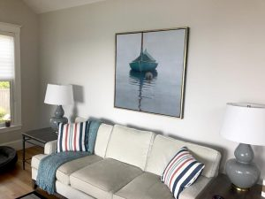 Robert Bolster painting of green sailboat hanging over couch