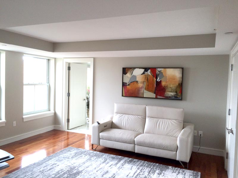 Red Natasha Barnes abstract painting over white couch in Boston condo