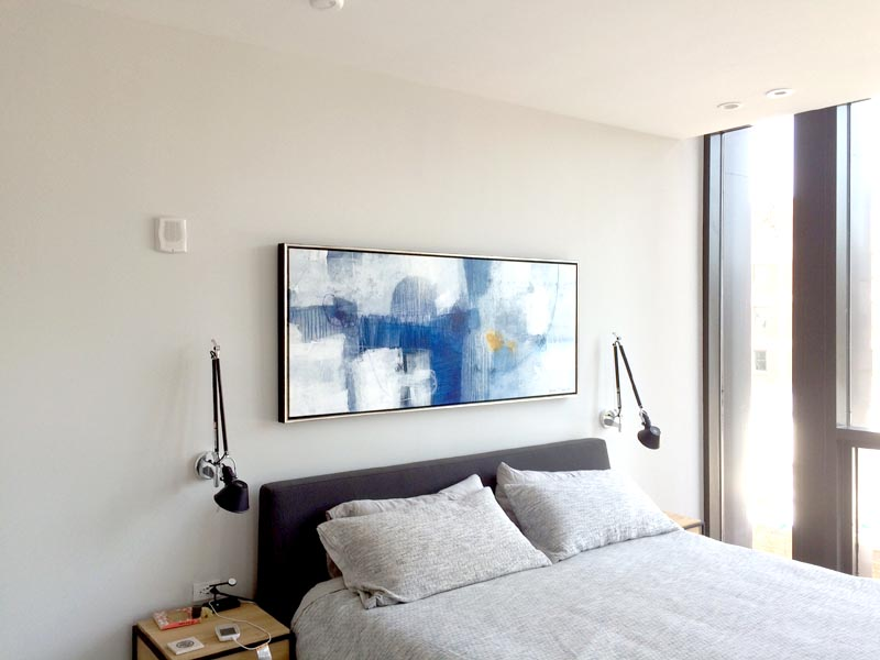 Horizontal Abstract painting hanging over bed in Boston Condo
