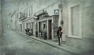 photo of woman walking down street in paris with baquette