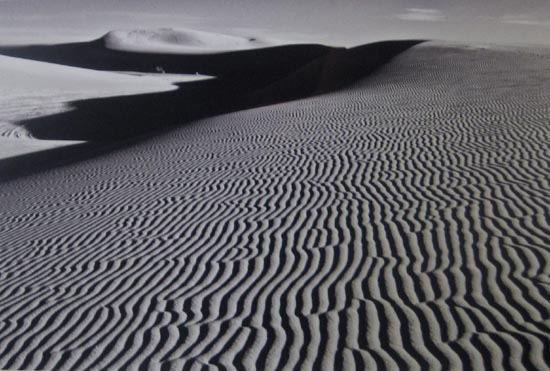 Black and white photograph of desert with ripples in sand