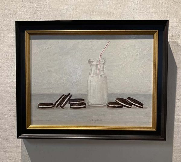 Framed Patti Zeigler painting of oreos scattered next to bottle of milk with straw