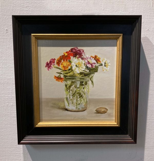 Framed Patti Zeigler painting of zinnias in a mason jar vase with a small sea shell