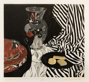 Sherrie Wolf print of cookies, a red tin, a vase, and fabric
