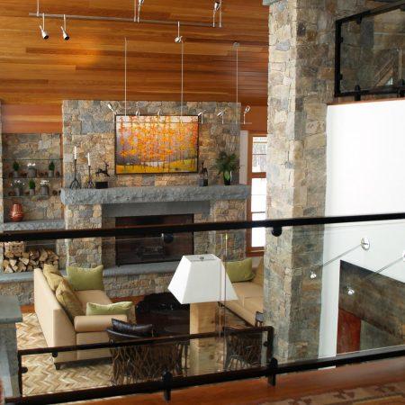 Jeff Koehn painting of trees over stone fireplace in Attitash, NH ski lodge home